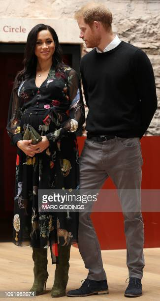 Britain's Meghan Duchess of Sussex and Britain's Prince Harry Duke of Sussex reacts as they visit Bristol Old Vic theatre in Bristol southwest...