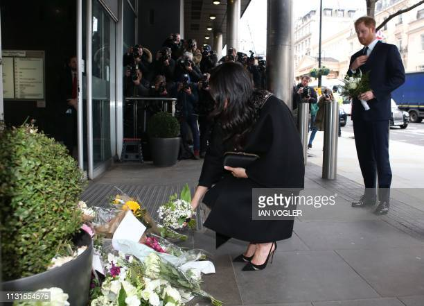 Britain's Meghan Duchess of Sussex and Britain's Prince Harry Duke of Sussex add bouquets of flowers to a pile of floral tributes at the New Zealand...