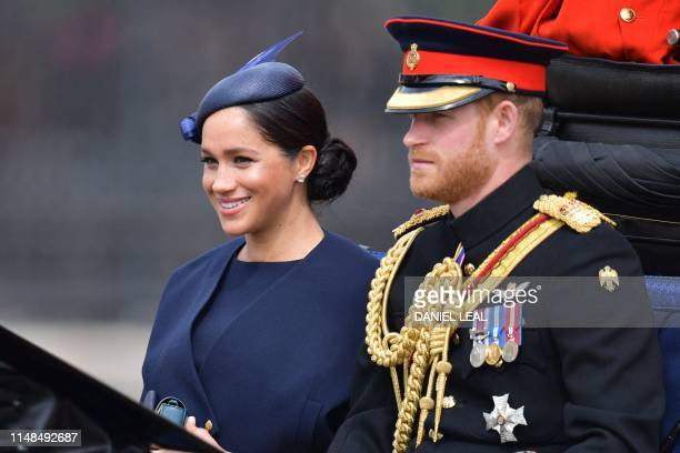 Britain's Meghan Duchess of Sussex and Britain's Prince Harry Duke of Sussex make their way in a horse drawn carriage to Horseguards parade ahead of...