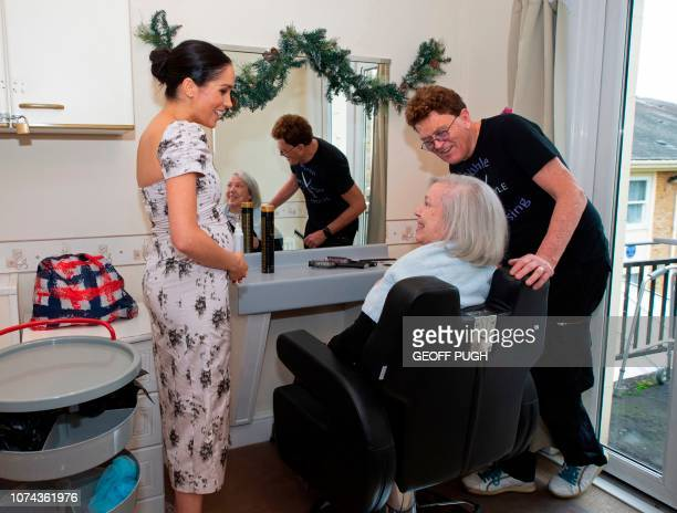 Britain's Meghan Duchess of Sussex chats to Biddy de Nordwall and hairdresser Michael Anthony Shelton during a visit to the Royal Variety Charity's...
