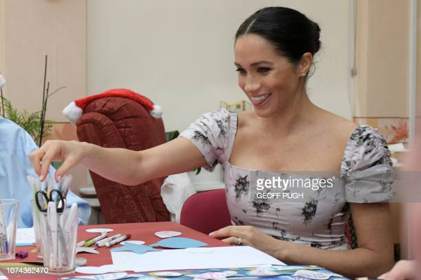 Britain's Meghan Duchess of Sussex joins in making Christmas decorations during her visit to the Royal Variety Charity's residential nursing and care...