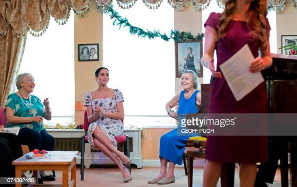 Britain's Meghan Duchess of Sussex listens to a singer during her visit to the Royal Variety Charity's residential nursing and care home Brinsworth...