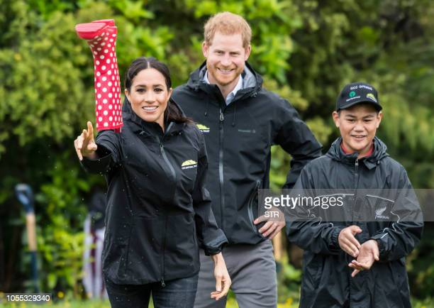 Britain's Meghan, Duchess of Sussex participates in a gumboot throwing competition with Prince Harry after unveiling a plaque dedicating 20 hectares...