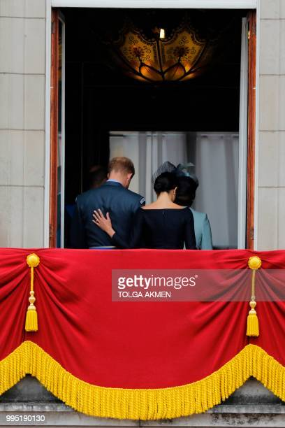 Britain's Meghan Duchess of Sussex puts her hand on Britain's Prince Harry Duke of Sussex's back as they leave the balcony of Buckingham Palace on...