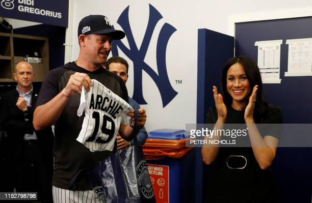 Britain's Meghan Duchess of Sussex reacts as she is presented with gifts for her newborn son Archie as they meet New York Yankees players ahead of...