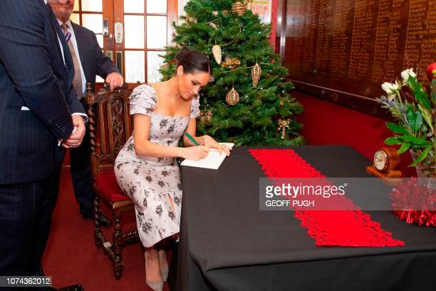 Britain's Meghan Duchess of Sussex signs a book during her visit to the Royal Variety Charity's residential nursing and care home Brinsworth House in...