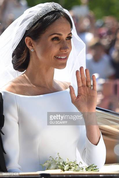 TOPSHOT Britain's Meghan Duchess of Sussex waves from the Ascot Landau Carriage with her husband Prince Harry during their carriage procession on the...