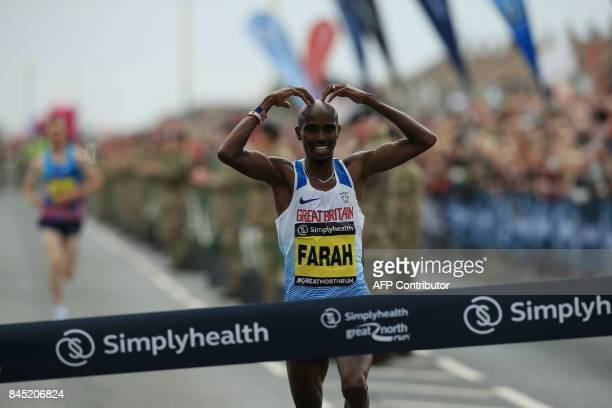 Britain's Mo Farah does his trademark Mobot gestures as he approaches the finish line to win the men's elite race of the Great North Run halfmarathon...