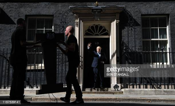 Britain's new Prime Minister Boris Johnson waves on the step of 10 Downing Street in London on July 24 2019 as technicians remove the lecturn after...