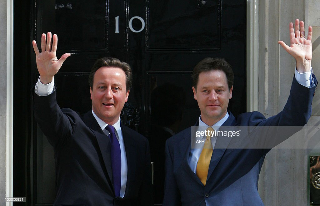 Britain's new Prime Minister David Cameron (L) and new Deputy Prime Minister Nick Clegg, wave as they pose for pictures outside 10 Downing Street in London, on May 12, 2010. British business leaders welcomed the new government under Prime Minister David Cameron Wednesday, but warned it must put cutting the country's record public debt 'at the top of the agenda'. AFP PHOTO/Geoff Caddick