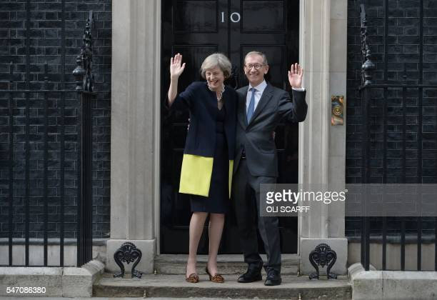 Britain's new Prime Minister Theresa May and her husband Philip John May wave outside the door of 10 Downing Street in central London on July 13 2016...