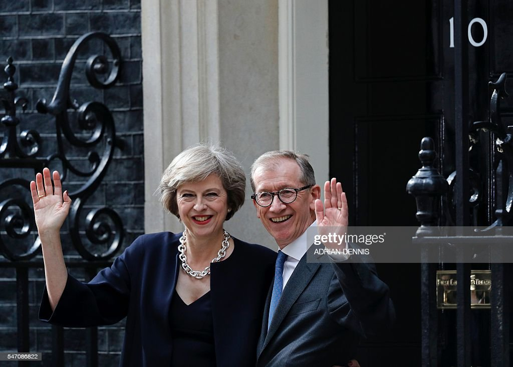 Britain's new Prime Minister Theresa May and her husband Philip John (R) wave outside 10 Downing Street in central London on July 13, 2016 on the day she takes office following the formal resignation of David Cameron. Theresa May took office as Britain's second female prime minister on July 13 charged with guiding the UK out of the European Union after a deeply devisive referendum campaign ended with Britain voting to leave and David Cameron resigning. / AFP / Adrian DENNIS