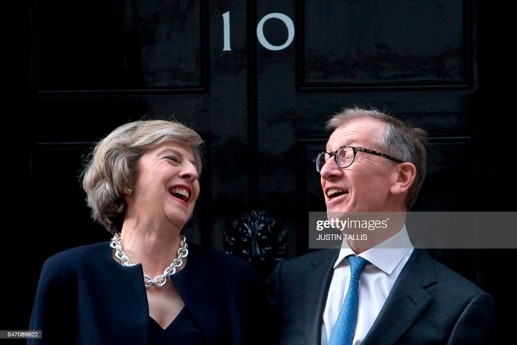 Britain's new Prime Minister Theresa May (L) and her husband Philip John May (R) laugh together outside the door of 10 Downing Street in central London on July 13, 2016 on the day that Theresa May takes office following the formal resignation of David Cameron. Theresa May took office as Britain's second female prime minister on July 13 charged with guiding the UK out of the European Union after a deeply devisive referendum campaign ended with Britain voting to leave and David Cameron resigning. TALLIS