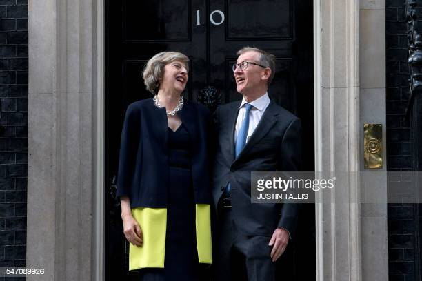 Britain's new Prime Minister Theresa May and her husband Philip John May laugh together outside the door of 10 Downing Street in central London on...