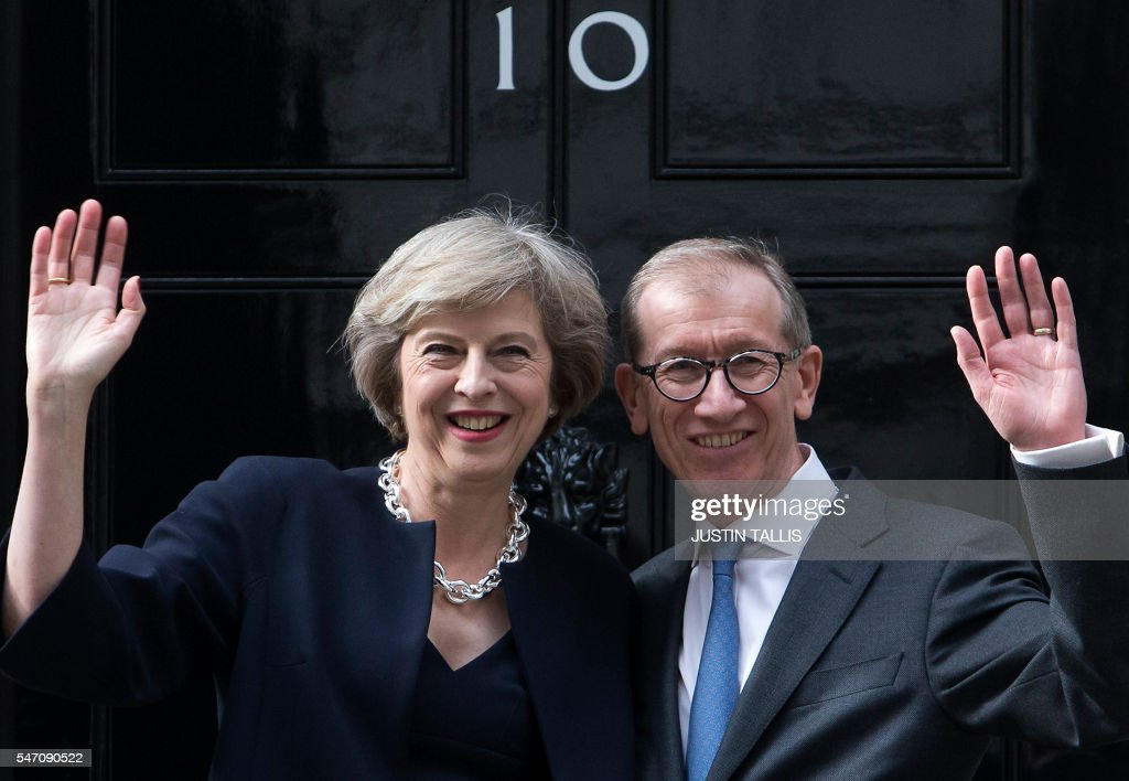 Britain's new Prime Minister Theresa May (L) and her husband Philip John (R) wave outside 10 Downing Street in central London on July 13, 2016 on the day she takes office following the formal resignation of David Cameron. Theresa May took office as Britain's second female prime minister on July 13 charged with guiding the UK out of the European Union after a deeply devisive referendum campaign ended with Britain voting to leave and David Cameron resigning. TALLIS