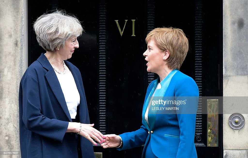 Britain's new Prime Minister Theresa May (L) is greeted by Scotland's First Minister Nicola Sturgeon (R) as she arrives for talks at Bute House, in Edinburgh, on July 15, 2016. Theresa May visited Scotland for talks with the First Minister less than 48 hours after taking office as British prime minister. / AFP / Lesley Martin