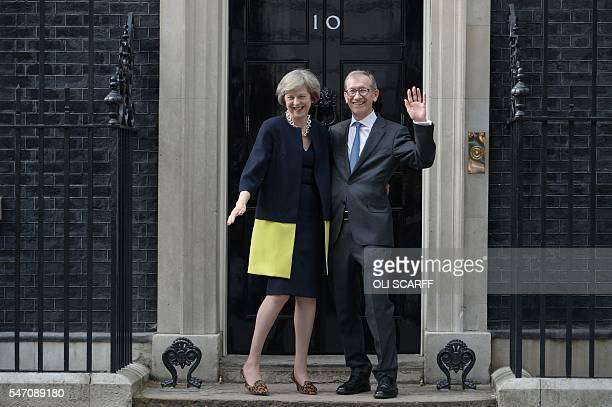 Britain's new Prime Minister Theresa May laughs as her husband Philip John waves outside 10 Downing Street in central London on July 13 2016 on the...