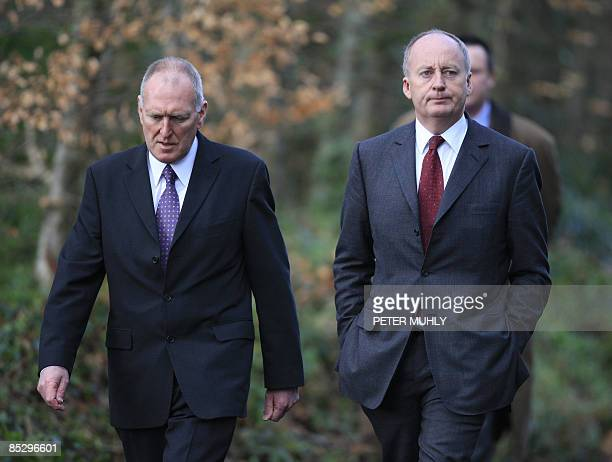 Britain's Northern Ireland Secretary Shaun Woodward and Criminal Justice Minister Paul Goggins walk together from the back gate of the Massereene...