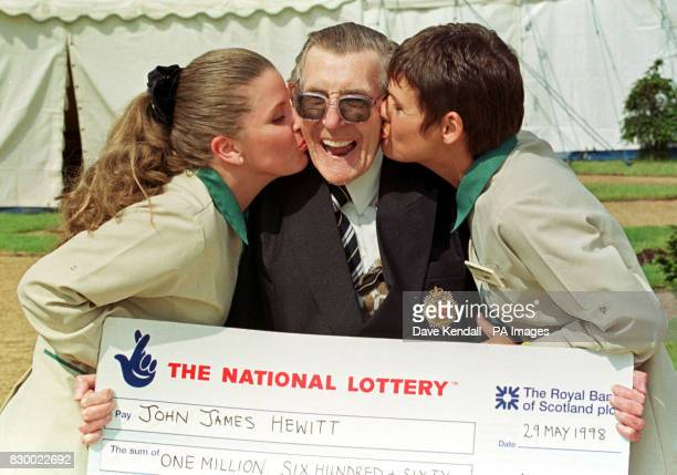 Britain's oldest Lottery winner Jack Hewitt 79 from Merseyside receives a kiss from the Asda Lottery till girls Samantha and Lynn who sold him his...