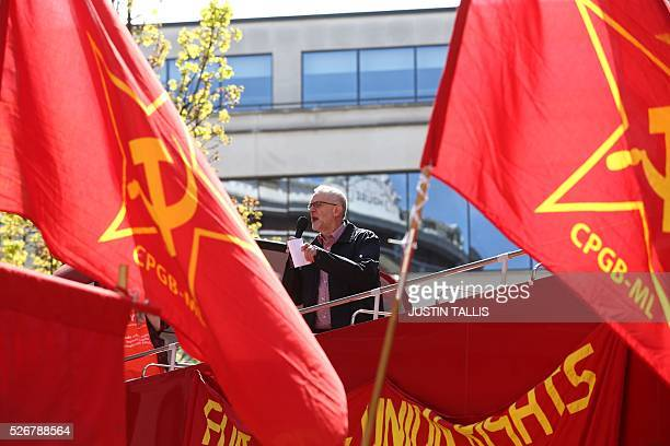 Britain's opposition Labour Party leader Jeremy Corbyn gives a speech from the top of a doubledecker bus as Communist Party of Great Britain flags...