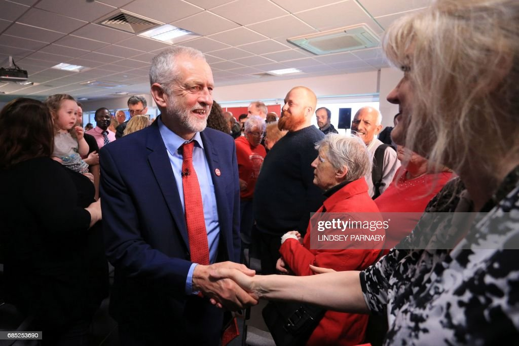 Britain's opposition Labour Party Leader Jeremy Corbyn shakes hands with a supporter after making a speech, at Peterborough Football Club in Peterborough, central England on May 19, 2017, as campaigning continues in the build up to the general election on June 8. / AFP PHOTO / Lindsey Parnaby