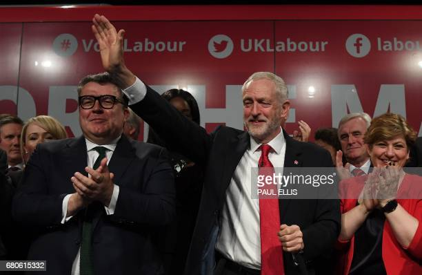 Britain's opposition Labour party Leader Jeremy Corbyn waves as he stands with Britain's opposition Labour party's Deputy Leader Tom Watson and...