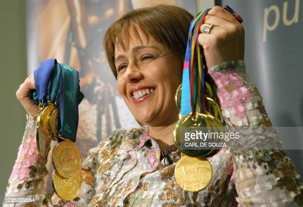 Britain's paralympian Dame Tanni Grey Thompson holds up her gold medals at a press conference in London as she announces her decision to retire from...