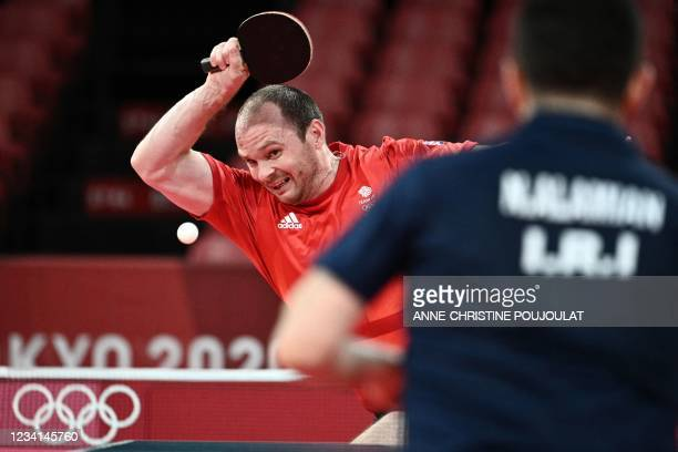 Britain's Paul Drinkhall hits a shot to Iran's Nima Alamian during their men's singles round 1 table tennis match at the Tokyo Metropolitan Gymnasium...