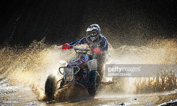 Britain's Paul Winrow goes through a water splash on his quad bike on his way to winning the main quad and sidecar race during the 2012 RHL Weston...
