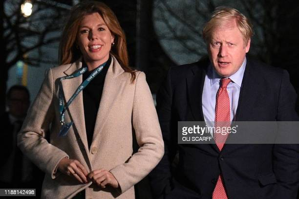 Britain's Prime Minister and Conservative leader Boris Johnson and his partner Carrie Symonds arrive at the count centre in Uxbridge west London on...