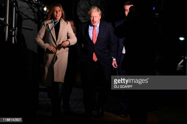 Britain's Prime Minister and Conservative leader Boris Johnson and his partner Carrie Symonds arrive at the count centre in Uxbridge, west London, on...