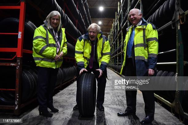 TOPSHOT Britain's Prime Minister and Conservative leader Boris Johnson looks at tryes in a warehouse with CEO Alan Ferguson and Conservative...