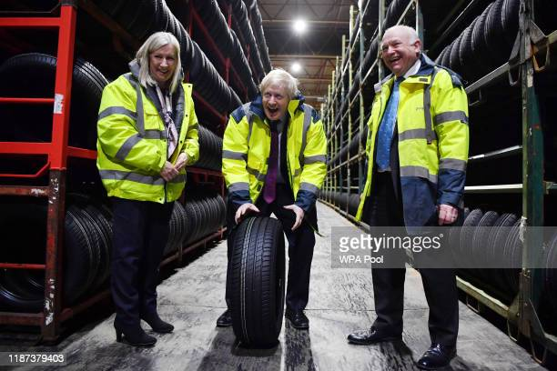 Britain's Prime Minister and Conservative leader Boris Johnson looks at tryes in a warehouse with CEO Alan Ferguson and Conservative Parliamentary...