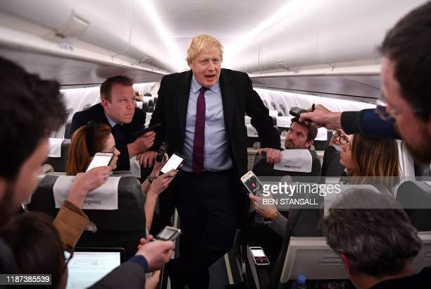 Britain's Prime Minister and Conservative party leader Boris Johnson talks with journalists as he travels aboard an aeroplane bound for Birmingham,...