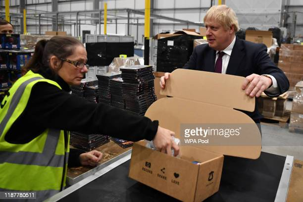 Britain's Prime Minister and Conservative party leader Boris Johnson helps out on the packing production line in a fulfillment centre for The Hut...