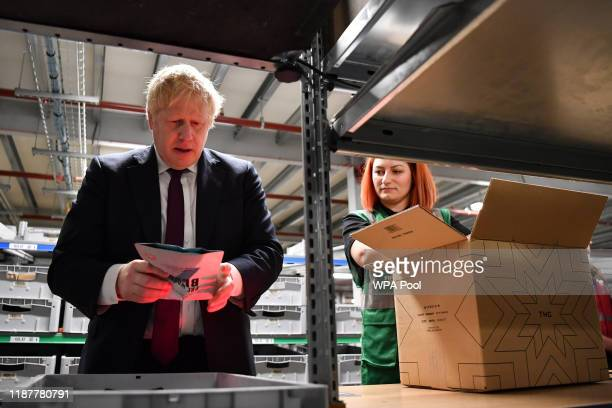 Britain's Prime Minister and Conservative party leader Boris Johnson helps to pack a box in a fulfillment centre for The Hut Group during a general...