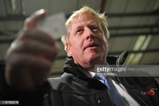 Britain's Prime Minister and Conservative party leader Boris Johnson reacts after reading the joke found inside one of the crackers during a visit to...