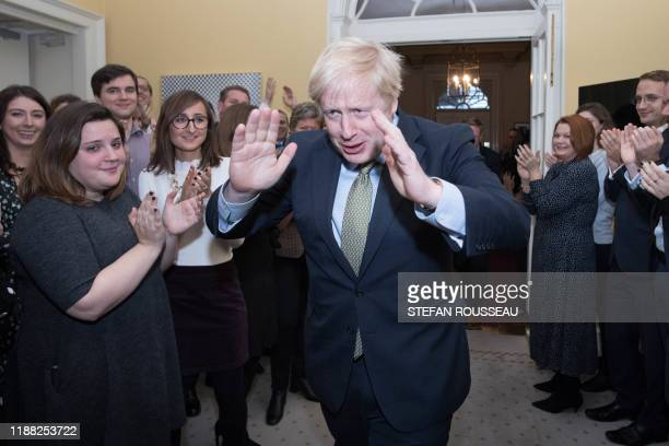 Britain's Prime Minister and Conservative Party leader Boris Johnson is greeted by staff as he arrives back at 10 Downing Street in central London on...