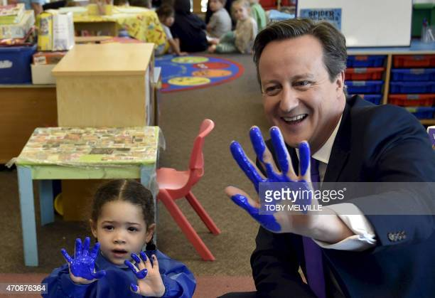 Britain's Prime Minister and leader of the Conservative party, David Cameron, shows his hand after participating in a hand-printing session at the...