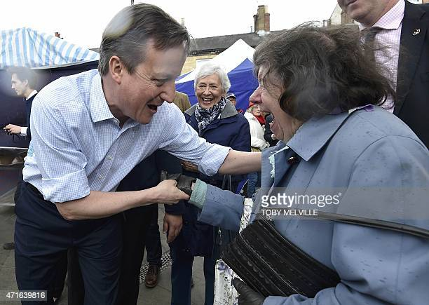 Britain's Prime Minister and leader of the Conservative Party David Cameron greets locals during a 'walkabout' whilst campaigning for the UK general...