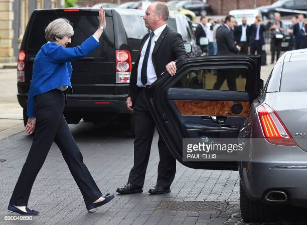 Britain's Prime Minister and Leader of the Conservative party Theresa May waves to supporters as she walks to a waiting car after speaking at a...