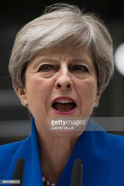 Britain's Prime Minister and leader of the Conservative Party Theresa May makes a statement outside 10 Downing Street in central London on June 9...
