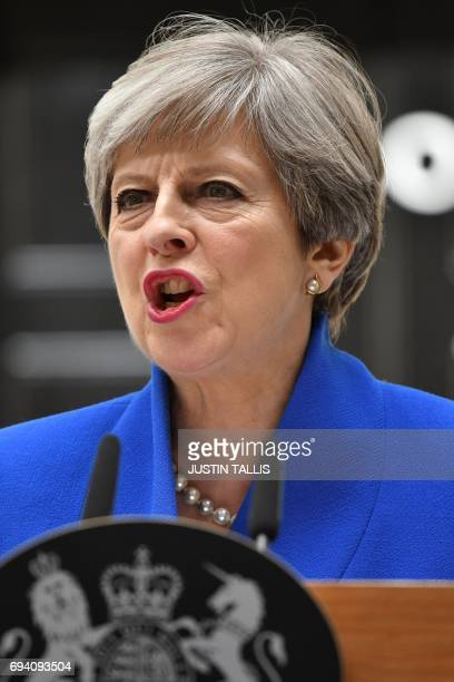 Britain's Prime Minister and leader of the Conservative Party Theresa May delivers a statement outside 10 Downing Street in central London on June 9...