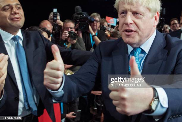 TOPSHOT Britain's Prime Minister Boris Johnson acknowledges the applause from Britain's Chancellor of the Exchequer Sajid Javid and members of his...