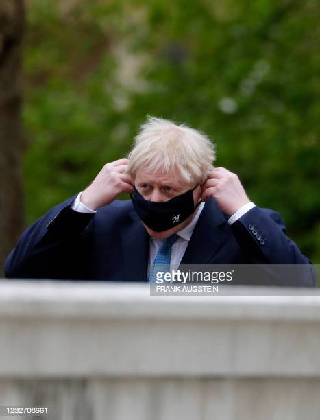 Britain's Prime Minister Boris Johnson adjusts his facemask as he arrives at the G7 foreign ministers meeting in London on May 5, 2021. - G7 foreign...