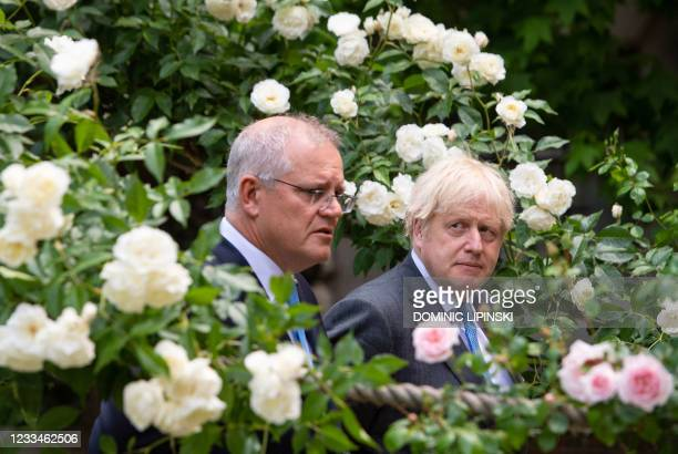 Britain's Prime Minister Boris Johnson and Australia's Prime Minister Scott Morrison walk in the garden of 10 Downing street in central London on...