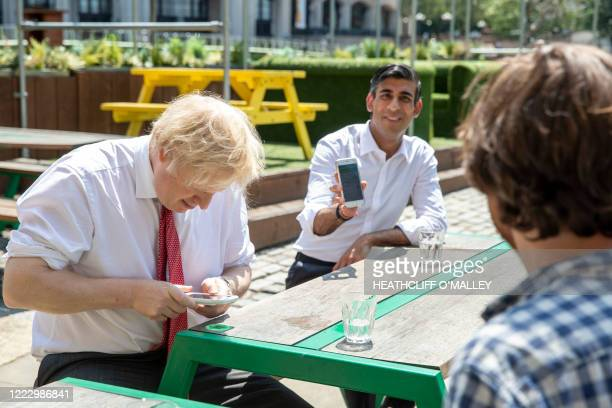 Britain's Prime Minister Boris Johnson and Britain's Chancellor of the Exchequer Rishi Sunak use their smartphones as they visit Pizza Pilgrims in...