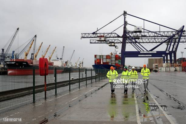 Britain's Prime Minister Boris Johnson , and Britain's Chancellor of the Exchequer Rishi Sunak walk past shipping containers during their visit to...