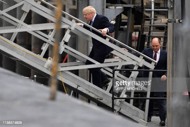 Britain's Prime Minister Boris Johnson and Britain's Defence Secretary Ben Wallace board Vanguardclass submarine HMS Victorious during a visit to...