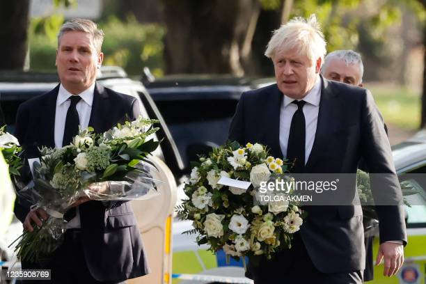 Britain's Prime Minister Boris Johnson and Britain's main opposition Labour Party leader Keir Starmer carry floral tributes as they arrivre at the...